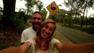 Two adults take selfie portrait standing near Emu warning sign video