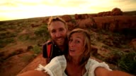 Two adults take selfie portrait with spectacular landscape at sunrise video