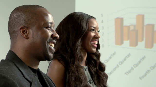 Two African American business man and woman discussing video