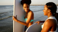 Two African American female friends prepare to go surfing video