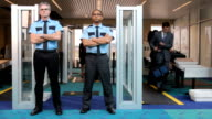 Two airport security guards standing in front of metal detector video