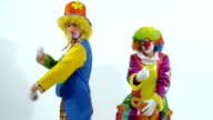 Two amusing clowns dancing together, when one of them drops the glasses video