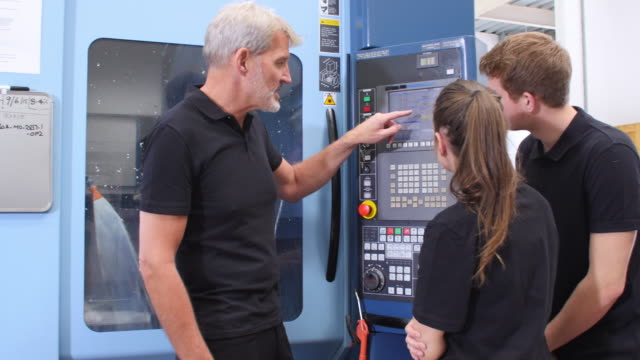 Two Apprentices Working With Engineer On CNC Machinery video