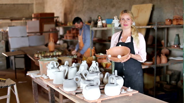two  artisans having ceramics in hands video