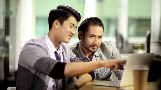 two asian corporate people discussing business in office video
