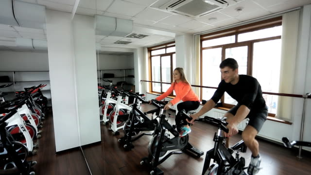 Two Athlete engaged on a stationary bike in gym video