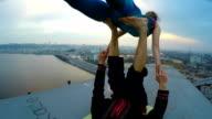 Two athletes doing acro yoga exercises on bridge, risky hobby, extreme sports video