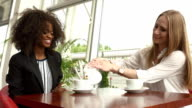 Two attractive mixed race businesswomen talking and making a deal while drinking coffee in the Coffee Shop video