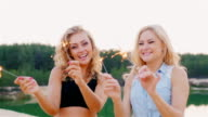 Two attractive woman with sparklers. Laughing on the beach video
