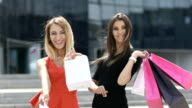 Two attractive women with shopping bags video