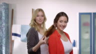 Two attractive young woman trying out new hairstyles in a modern bathroom  with a lot of fun video
