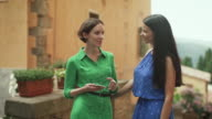 Two Attractive Young Women in Light Summer Dresses Have Conversation on Streets of European Town. video