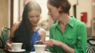 Two Attractive Young Women in Light Summer Dresses Relax and have Conversation in Street Coffee Shop. One Sharing something Exciting on her Mobile Phone with Other. video