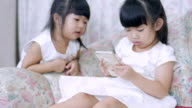 Two baby Girl enjoy playing smartphone video