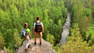 Two backpackers walk high rock above forest video