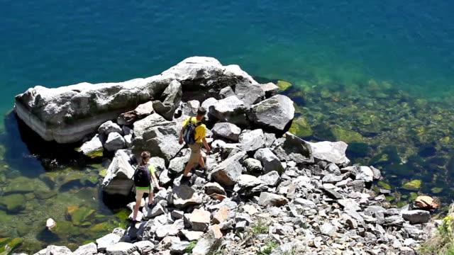 Two backpackers walk on rocky coast video