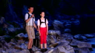 Two backpackers walk on rocky way video