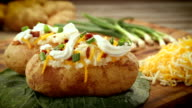 Two baked Russet potatoes fully garnished with cheese, chives, bacon and sour cream. video