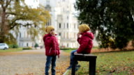 Two beautiful children, boy brothers, sitting on bench in beautiful renaissance castle Hluboka in the Czech Republic video
