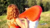 Two beautiful girl friends pillow fight on nature in sunset time video