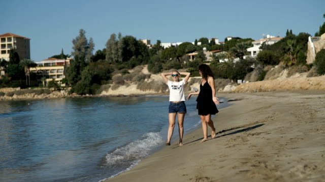 Two beautiful girls are walking along the beach near the ocean video