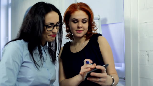 Two beautiful women discuss important information at office video