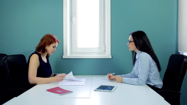 Two beautiful women sign contract at office video