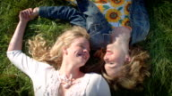 Two Best Friends Lay In A Field, Holding Hands, And Chatting And Laughing video