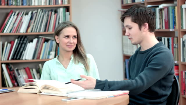 Two best friends talking and laughing over good books in library video