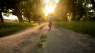two bicyclists riding on a dirt road video
