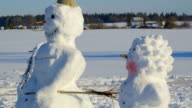 Two big snowman standing on the ground video