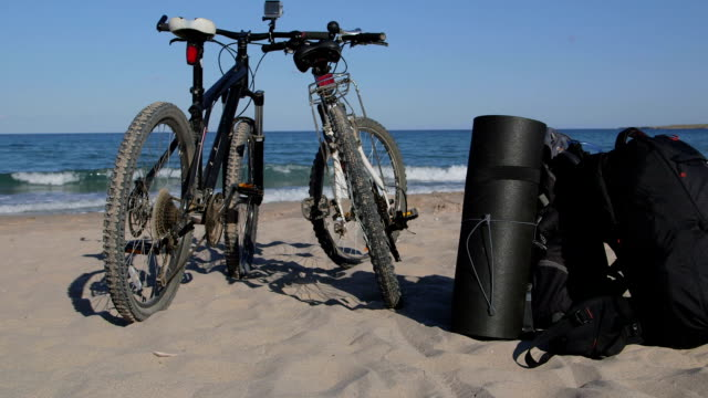 Two bikes with backpacks on the summer beach video