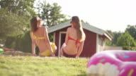 Two bikini girls sitting by swimming pool video
