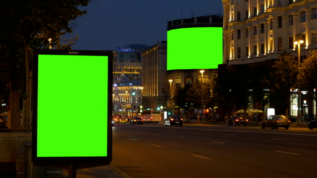 Two billboards with a green screen. In the evening, on a busy street. video