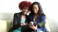 Two black businesswomen talking, looking at folder video