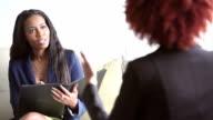 Two black businesswomen talking, one taking notes video