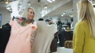 Two blond girls are choosing between a white and a pink dress while standing in a department store. video