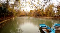 Two Blue Boats Moor Fog Floats under Pond with Fountain around Green and Yellow Trees Park Urfa video