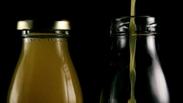 Two bottles on a black background with juice. Slow motion video