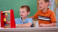 Two boys at school counting with abacus video