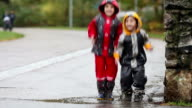 Two boys, brothers, jumping in muddy puddle in the park, autumn time on a rainy day video
