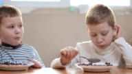 Two boys eatting flakes with milk at home video