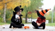 Two boys in the park with Halloween costumes, having fun video
