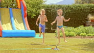 SLO MO Two boys jumping around water sprinkler video
