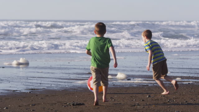 Two boys playing with beach ball, slow motion video