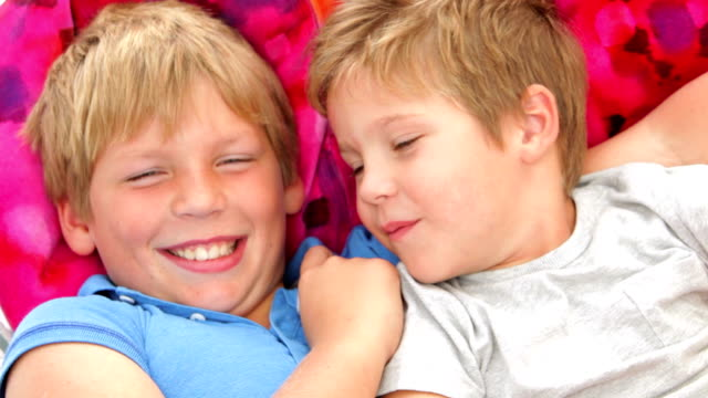 Two Boys Relaxing In Garden Hammock Together video