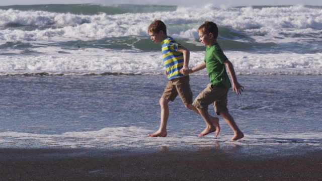 Two boys running at beach together, slow motion video