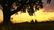SLO MO Two boys swinging on the swing at sunset video