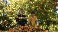 Two boys throwing fall leaves, slow motion video