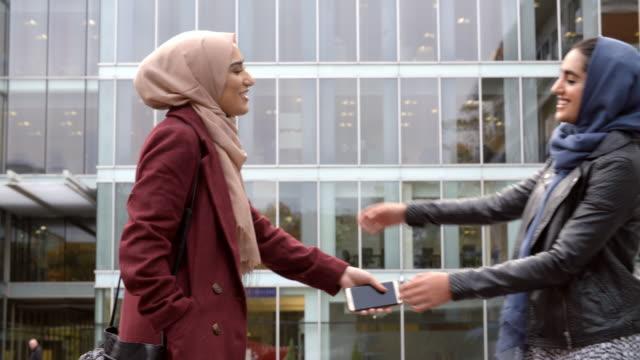 Two British Muslim Women Friends Meeting Outside Office video